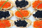 A picture of a plate of black and red caviar sandwiches