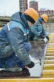 image of concrete pouring  - construction worker at construction site assembling falsework for concrete pouring - JPG