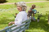 Happy woman sitting on bench while man watering young plant at the park