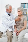 Male doctor checking senior patients heartbeat using stethoscope