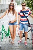 Portrait of girl and guy with bicycles looking at camera in the park