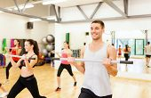 fitness, sport, training, gym and lifestyle concept - group of smiling people working out with barbe