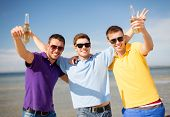 summer, holidays, vacation and people concept - group of male friends having fun on the beach with b