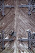 picture of entryway  - Imposing entryway of home with old weathered doors and heavy black wrought iron hardware.