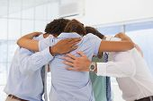 Rear view of business team with heads together forming a huddle