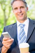 Portrait of smiling businessman with mobile phone and disposable cup at park