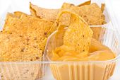 foto of nachos  - nachos chips with cheese sauce in plastic container isolated on white background - JPG