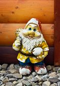 image of gnome  - Shabby old figure of a garden gnome against the wooden planking background outdoors - JPG