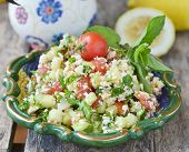 image of tabouleh  - vegetables salad in to ornamental plate on wooden table  - JPG