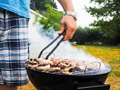 foto of agaricus  - Male person with food tweezers barbequing with lot - JPG
