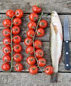 foto of mullet  - raw mullet with cherry tomatoes on wooden table - JPG