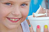 stock photo of braces  - Little Caucasian girl with colorful braces on her teeth and ice cream in styrofoam cup - JPG