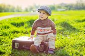 foto of headdress  - small child in a headdress playfully climbed a suitcase