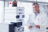 stock photo of scientist  - Scientist standing in lab coat holding a document in laboratory - JPG