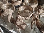 stock photo of mason  - A small grouping of clean ready to fill mason jars decorated with simple burlap bows - JPG