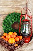 picture of kerosene lamp  - Kerosene lamp with wreath and oranges in wicker basket on wooden planks background - JPG