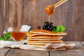 pic of carbohydrate  - Stack of pancakes with mint and berries on rustic wooden background - JPG