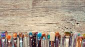 pic of bristle brush  - Row of artist paintbrushes closeup on old wooden rustic background - JPG
