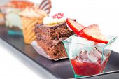stock photo of fancy cake  - delicious strawberry cake with cream in front of little chocolate and coffee cakes on black dish - JPG