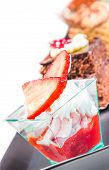 picture of fancy cakes  - delicious strawberry cake with cream in front of little chocolate and coffee cakes on black - JPG