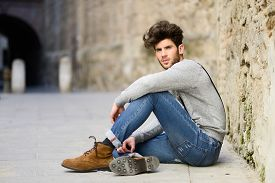 foto of suspenders  - Portrait of young man wearing suspenders sitting on the floor in urban background - JPG