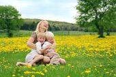stock photo of tickle  - A happy young mother is sitting in in a meadow of dandelion flowers with her two children laughing tickling and playing - JPG