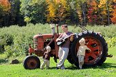 picture of tractor  - A Father and his two young boy children are relaxing on a farm playing guitar by an old tractor in the autumn woods - JPG