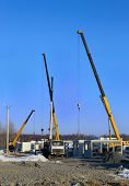 stock photo of lift truck  - Building site with a crane trucks that unloads trucks and works on the construction - JPG