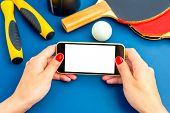 picture of ping pong  - Using smartphone with white screen on table with ping pong rackets - JPG