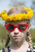 foto of cheater  - funny young pretty caucasian girl face in yellow dandelions garland on the head and red sunglasses  - JPG