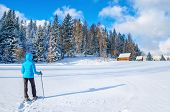 image of down jacket  - Young woman in blue down jacket walking towards remote mountain hut during cold winter - JPG