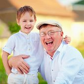 stock photo of grandpa  - portrait of happy grandpa and grandson outdoors - JPG