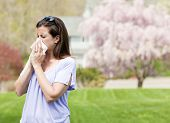 image of blowing  - Woman outside blowing nose with a tissue  - JPG
