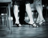 stock photo of black heel  - Feet and legs of young women wedding guest in high heel shoes and cocktail party dress in wedding reception blue black and white toned photo.