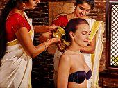stock photo of panchakarma  - Young sitting woman having ayurveda spa treatment - JPG