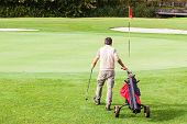 stock photo of golf bag  - a golf player playing on a beautiful golf course and a golf bag full of golf clubs - JPG