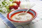 stock photo of porridge  - Porridge and red apples on a wooden table - JPG