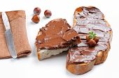 image of hazelnut  - Two slices of bread with chocolate cream and hazelnuts white isolated front view - JPG