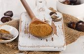 stock photo of ground nut  - Raw Organic ground Nutmeg on a white wooden cutting board - JPG