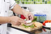 image of hamburger  - Chef putting onion hamburger on the bun  - JPG