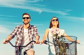 stock photo of angle  - Low angle view of cheerful young couple smiling and riding on bicycles - JPG