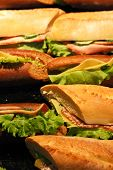 foto of salami  - Sandwiches made with fresh baked french bread salami bacon cheese and salad vegetables - JPG
