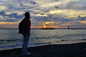 stock photo of humility  - summer beautiful girl at sunset on the sea - JPG