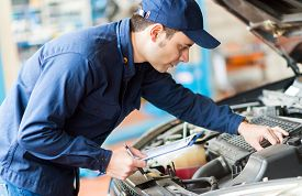 stock photo of overhauling  - Portrait of a mechanic at work in his garage - JPG