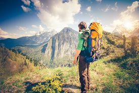 stock photo of boy scout  - Young Man Traveler with backpack relaxing outdoor with rocky mountains on background Summer vacations and Lifestyle hiking concept - JPG