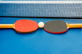 stock photo of ping pong  - Two table tennis or ping pong rackets and ball on a blue table with net - JPG