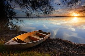 picture of divine  - Sublime scene and tranquil waters reflecting like a mirror as the divine sun sets casting its golden orange glow upon the clouds and highlighting the little boat as it rests on the shoreline waiting for tomorrows dreams and adventures - JPG