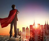 superhero businessman looking at city skyline at sunset. the concept of success, leadership and vict poster