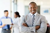 happy african salesman standing at car dealership with colleagues on background poster