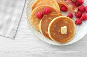Tasty breakfast with pancakes, bacon and raspberry on plate poster